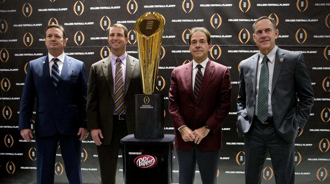 College football playoff coaches from left; Bob Stoops, of Oklahoma, Dabo Swenney, of Clemson, Nick Saban, of Alabama and Mark  Dontonio, of Michigan St., pose with the championship trophy after a news conference the college football awards at the College