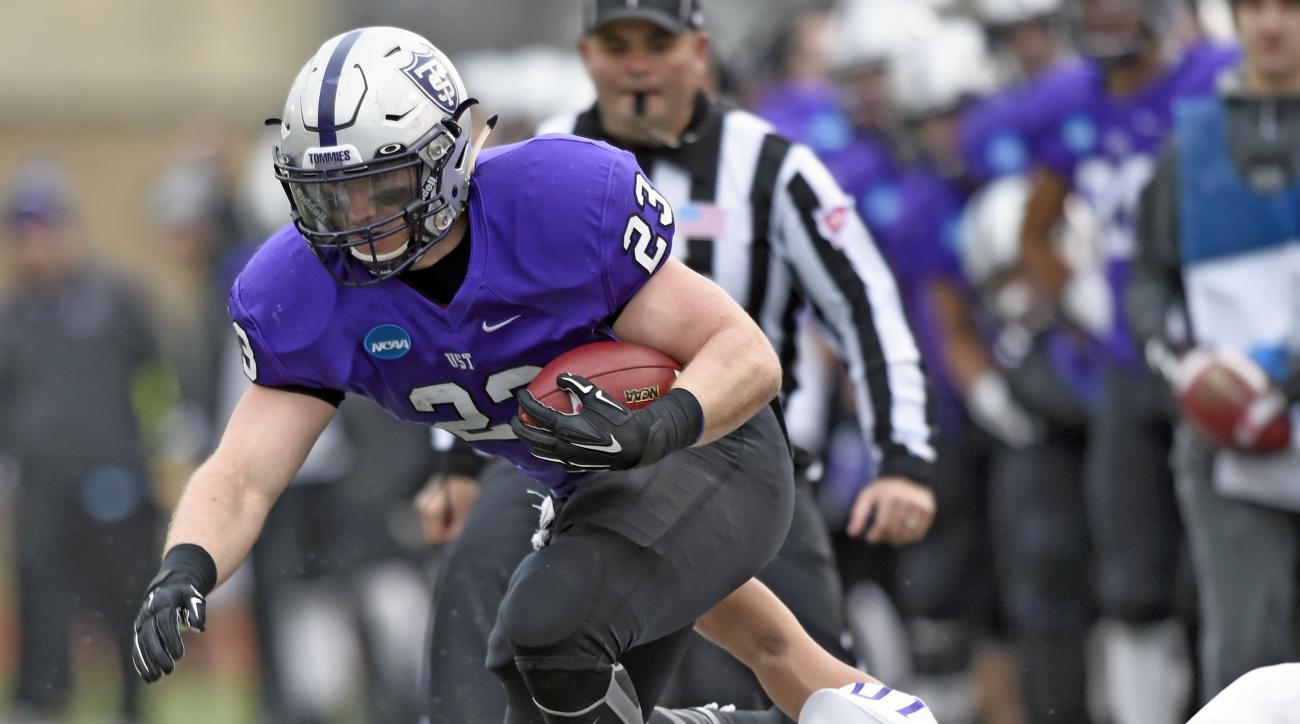 Linfield middle linebacker Skylor Elgarico (10) pulls St. Thomas running back Jordan Roberts (23) out of bounds during the first quarter during a Division III NCAA college football semifinal game on Saturday, Dec. 12, 2015, in St. Paul, Minn. (AP Photo/Ha
