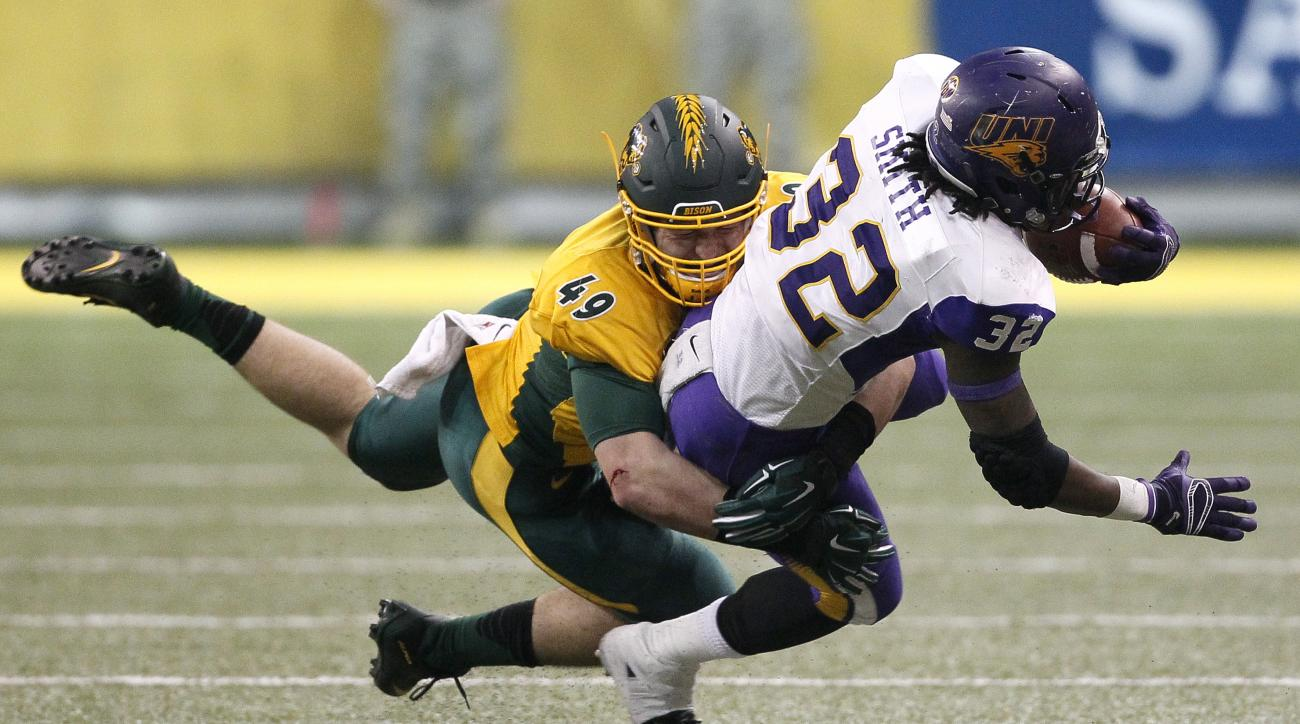 North Dakota State's NickDeLuca, left, tackles Northern Iowa's Tyvis Smith on a first down run in the first half of an NCAA college football game in the quarterfinals of the Football Championship Subdivision at the FargoDome Saturday, Dec. 12, 2015, in Fa
