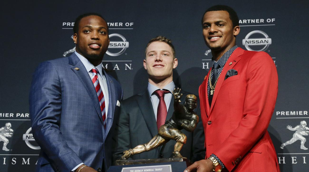Heisman Trophy finalists, from left, Alabama's Derrick Henry, Stanford's Christian McCaffrey and Clemson's Deshaun Watson pose for a photo with the Heisman Trophy before the start of the award presentation show, Saturday, Dec. 12, 2015, in New York. (AP P