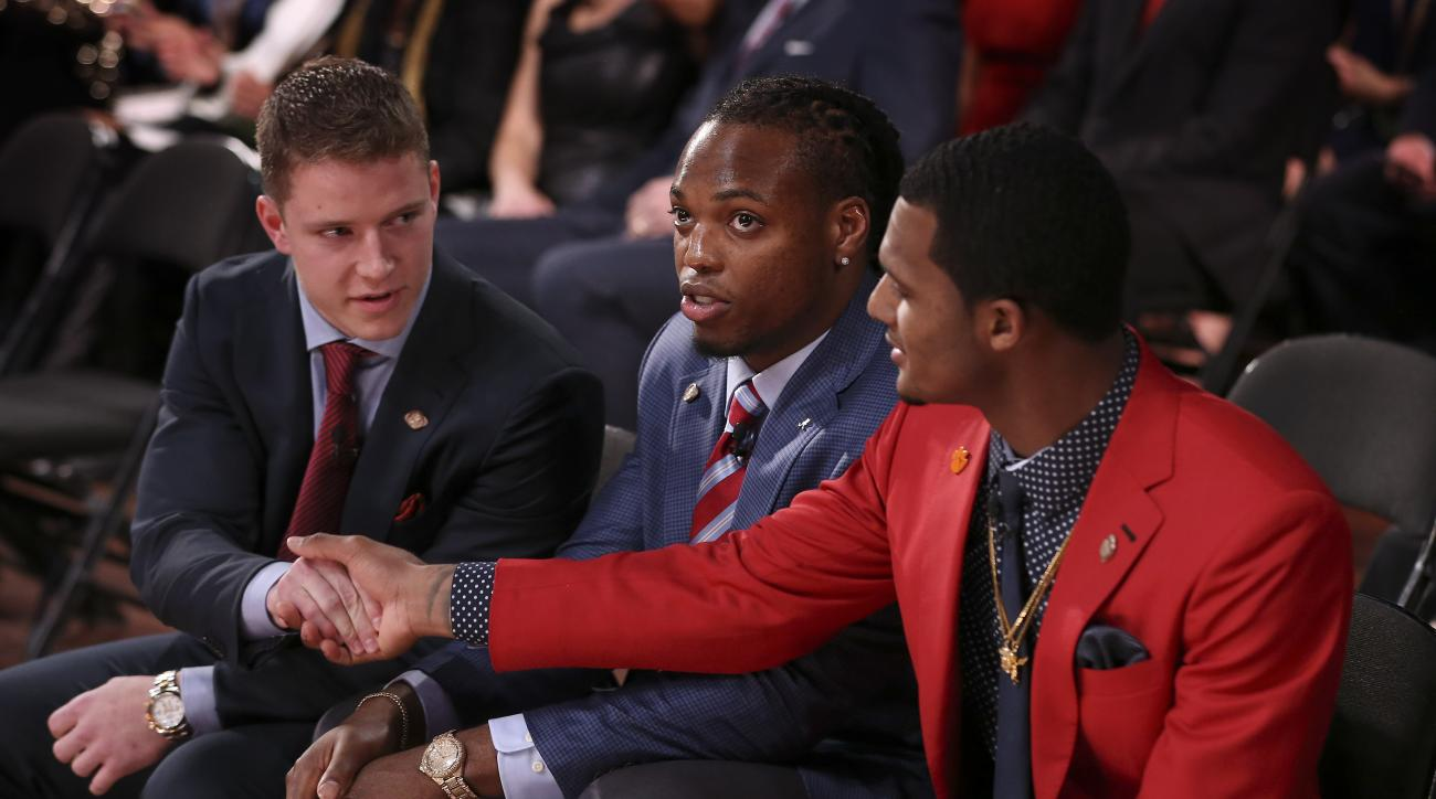 Heisman Trophy finalists, from left, Stanford's Christian McCaffrey and Clemson's Deshaun Watson, right, shake hands as Alabama's Derrick Henry looks on during the Heisman Trophy presentation show, Saturday, Dec. 12, 2015, in New York. Henry won the award