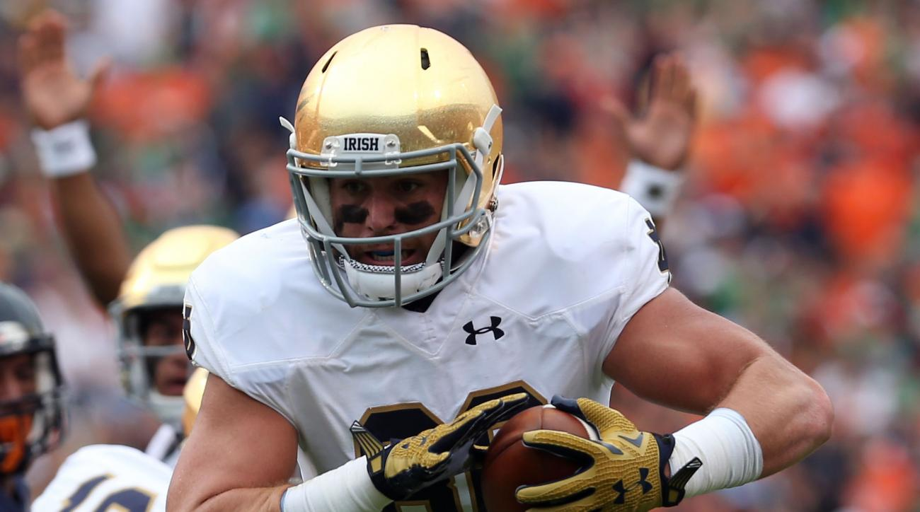 FILE - In this Sept. 12, 2015, file photo, Notre Dame tight end Durham Smythe (80) runs the ball in for a touchdown during an NCAA college football game against Virginia, in Charlottesville, Va. Notre Dame is expecting to get a bowl boost from two familia