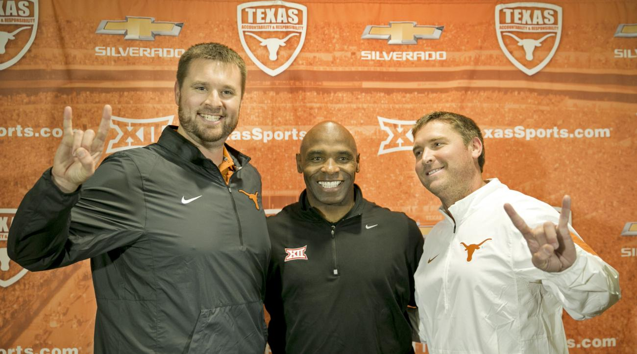 CORRECTS FROM MIKE TO MATT MATTOX- University of Texas NCAA college football head coach Charlie Strong, center, introduces two new assistant coaches, offensive line coach Matt Mattox, left, and offensive coordinator Sterlin Gilbert, during a news conferen