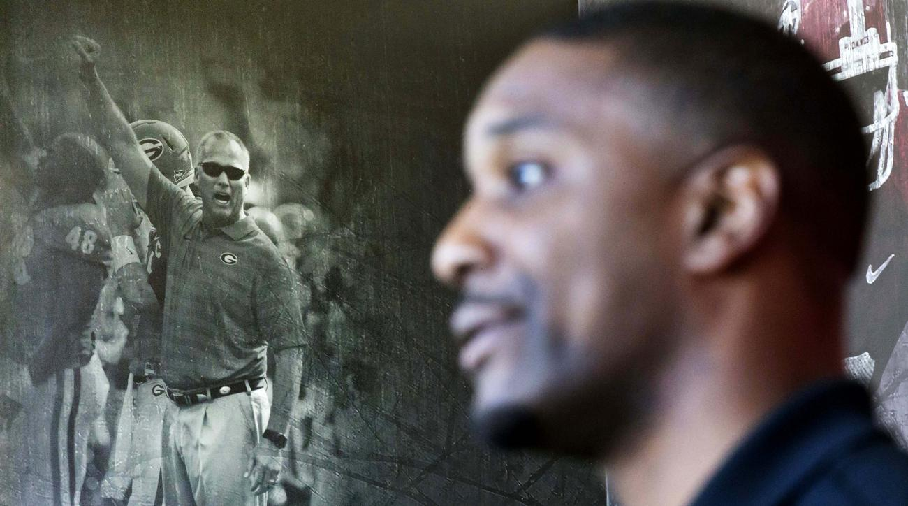 A mural of former Georgia football head coach Mark Richt stands in the background as interim head coach Bryan McClendon, right, speaks during a press conference Wednesday, Dec. 16, 2015, in Athens, Ga. A coaching change at Georgia has left McClendon with