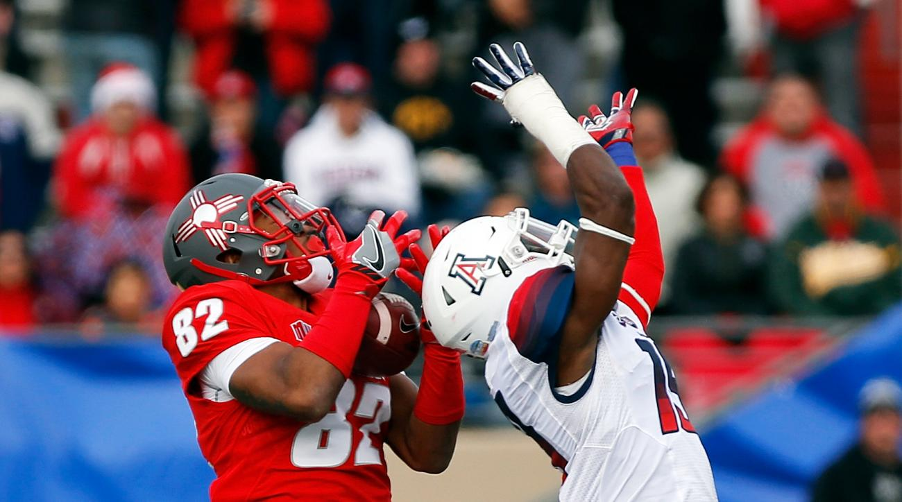 New Mexico wide receiver Delane Hart-Johnson (82) catches a pass before scoring a touchdown against the defense of Arizona cornerback Kwesi Mashack during the first half of the New Mexico Bowl NCAA college football game in Albuquerque, N.M., Saturday, Dec