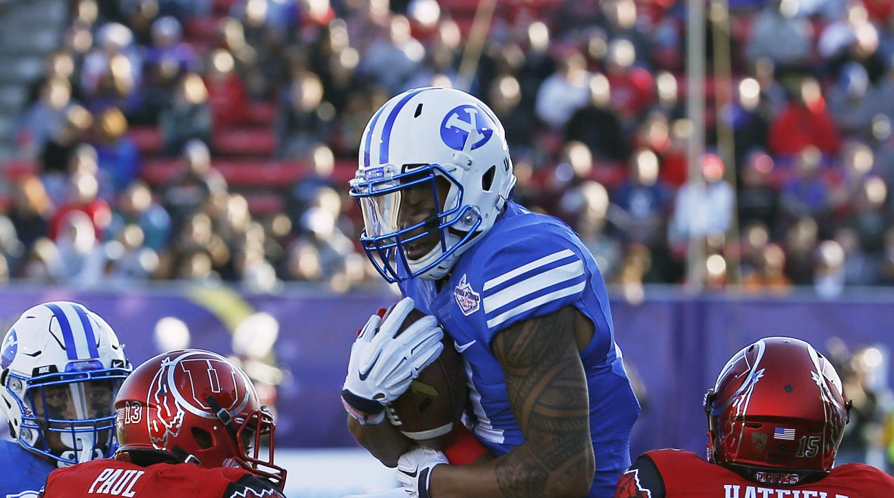 BYU wide receiver Terenn Houk catches a pass over Utah linebacker Gionni Paul (13) and defensive back Dominique Hatfield (15) during the first half of the Las Vegas Bowl NCAA college football game Saturday, Dec. 19, 2015, in Las Vegas. (AP Photo/John Loch