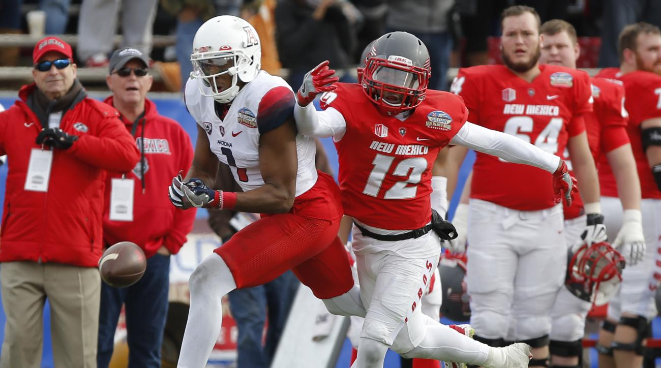 Arizona wide receiver Cayleb Jones, left, misses a reception as he's defended by New Mexico safety Ryan Santos during the first half of the New Mexico Bowl NCAA college football game in Albuquerque, N.M., Saturday, Dec. 19, 2015. Arizona won 45-37. (AP Ph