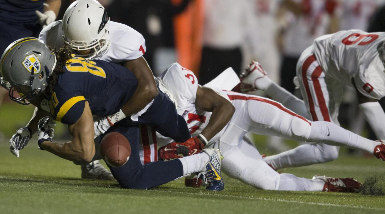 Marian wide receiver Krishawn Hogan (80) left, fumbles the ball after being tackled by Southern Oregon defensive back Julius Rucker (1) top left, and Mylz Blake (31), right, during the first half of the NAIA National Football Championship in Daytona Beach