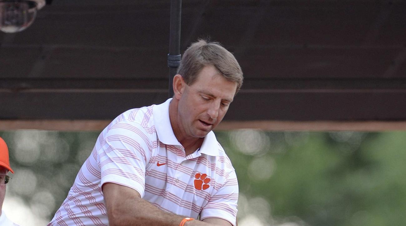 FILE - In this Sept. 6, 2014, file photo, Clemson coach Dabo Swinney rubs Howard's Rock before Clemson's NCAA college football game against South Carolina State in Clemson, S.C. Faith and football go together at Clemson, as they do at many prominent unive