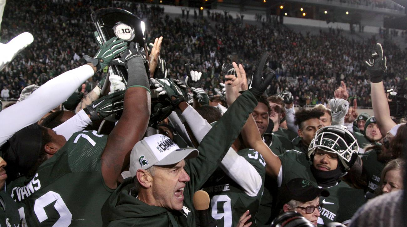FILE - In this Nov. 28, 2015, file photo, Michigan State coach Mark Dantonio, bottom, and players celebrate with their Big Ten East Division Championship trophy after beating Penn State 55-16 in an NCAA college football game in East Lansing, Mich. Perhaps