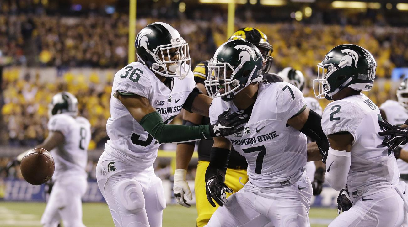 FILE - In this Dec. 5, 2015, file photo, Michigan State defensive back Demetrious Cox (7) celebrates with teammates after making an interception during the first half of the Big Ten championship NCAA college football game against Iowa in Indianapolis. Per