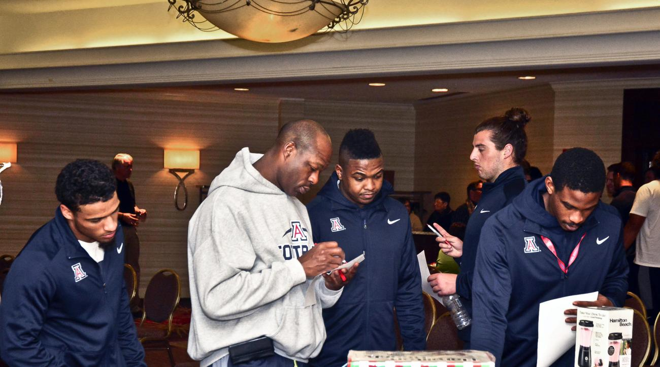 In this Dec. 19, 2015 photo provided by the The Gildan New Mexico Bowl, members of the Arizona football team walk around the gift suite at the New Mexico Bowl before their NCAA college football game against New Mexico in Albuquerque, N.M. NCAA rules allow