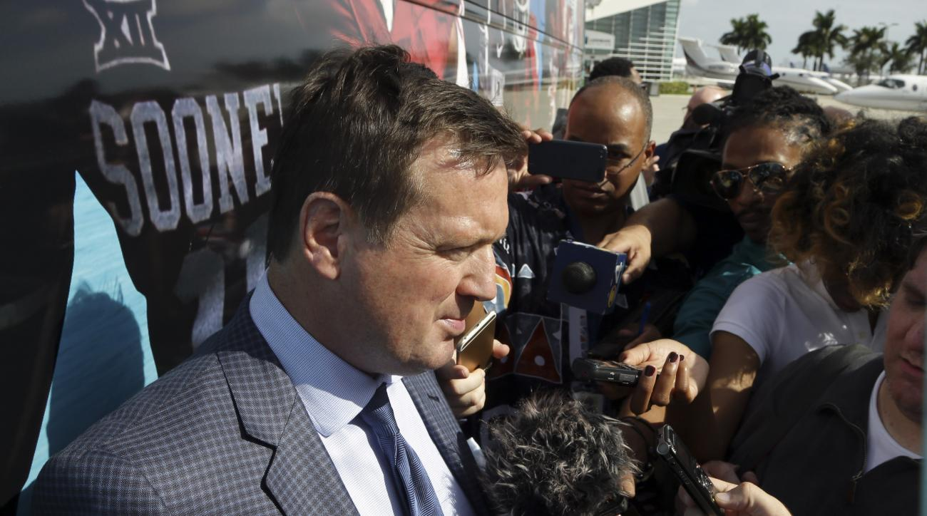 Oklahoma head coach Bob Stoops talks with the media after the team arrived in Miami, Saturday, Dec. 26, 2015. Oklahoma plays Clemson in the Orange Bowl NCAA college playoff semifinal Dec. 31 in Miami. (AP Photo/Lynne Sladky)