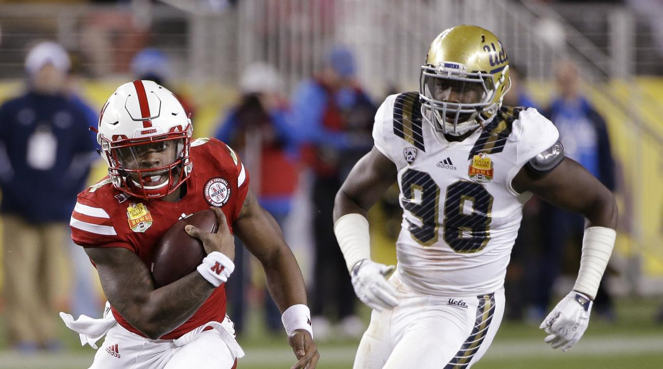 Nebraska quarterback Tommy Armstrong Jr., left, runs past UCLA defensive lineman Takkarist McKinley (98) during the first half of the Foster Farms Bowl NCAA college football game Saturday, Dec. 26, 2015, in Santa Clara, Calif. (AP Photo/Marcio Jose Sanche