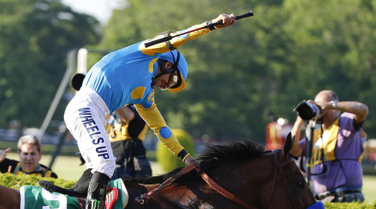 FILE - In this June 6, 2015, file photo, Victor Espinoza reacts after guiding American Pharoah across the finish line to win the Belmont Stakes horse race at Belmont Park in New York. American Pharoah started slow and carried a two-length lead through mos