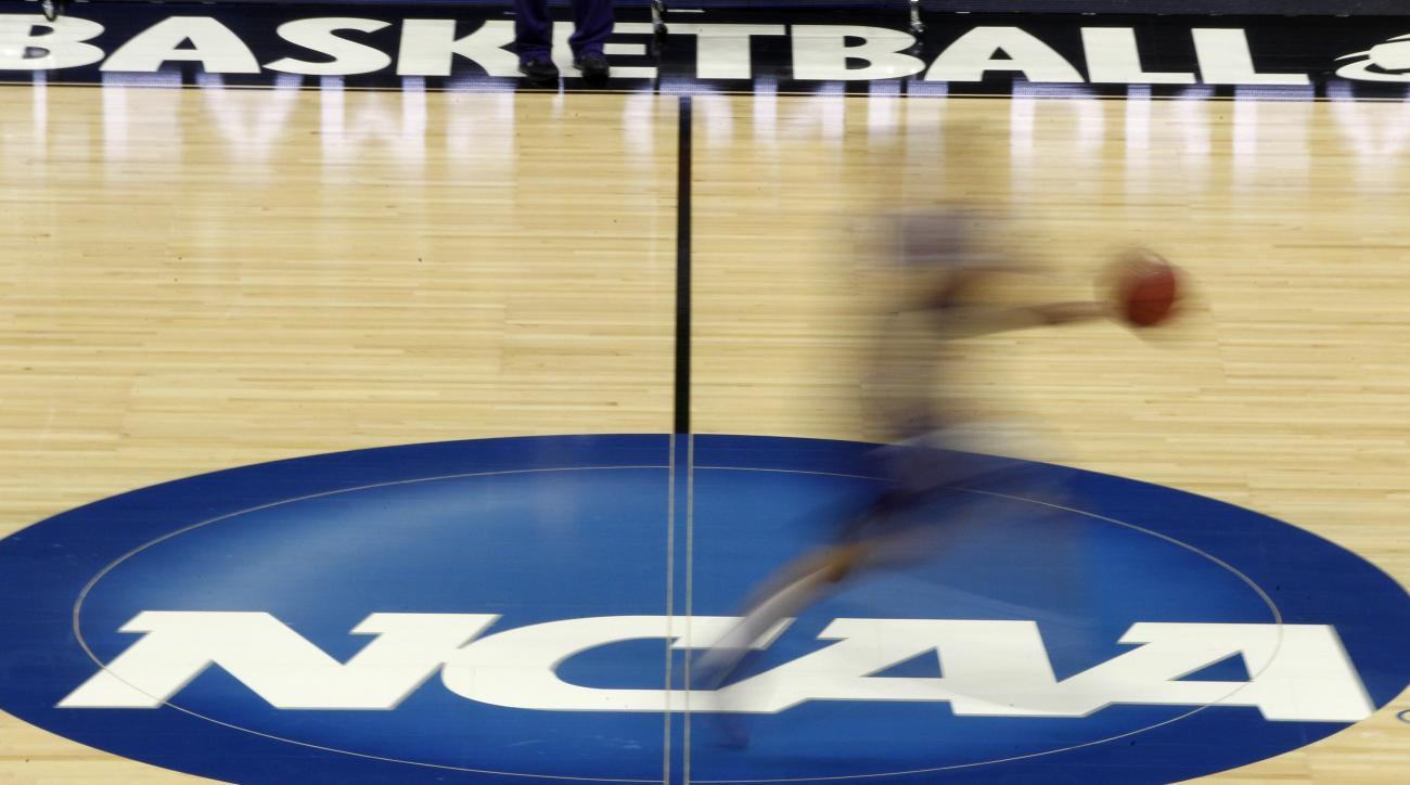 FILE - In this March 14, 2012, file photo made with a long exposure, a player runs across the NCAA logo at midcourt during practice in Pittsburgh before an NCAA tournament college basketball game. The NCAA last year cut in half the penalty for athletes wh
