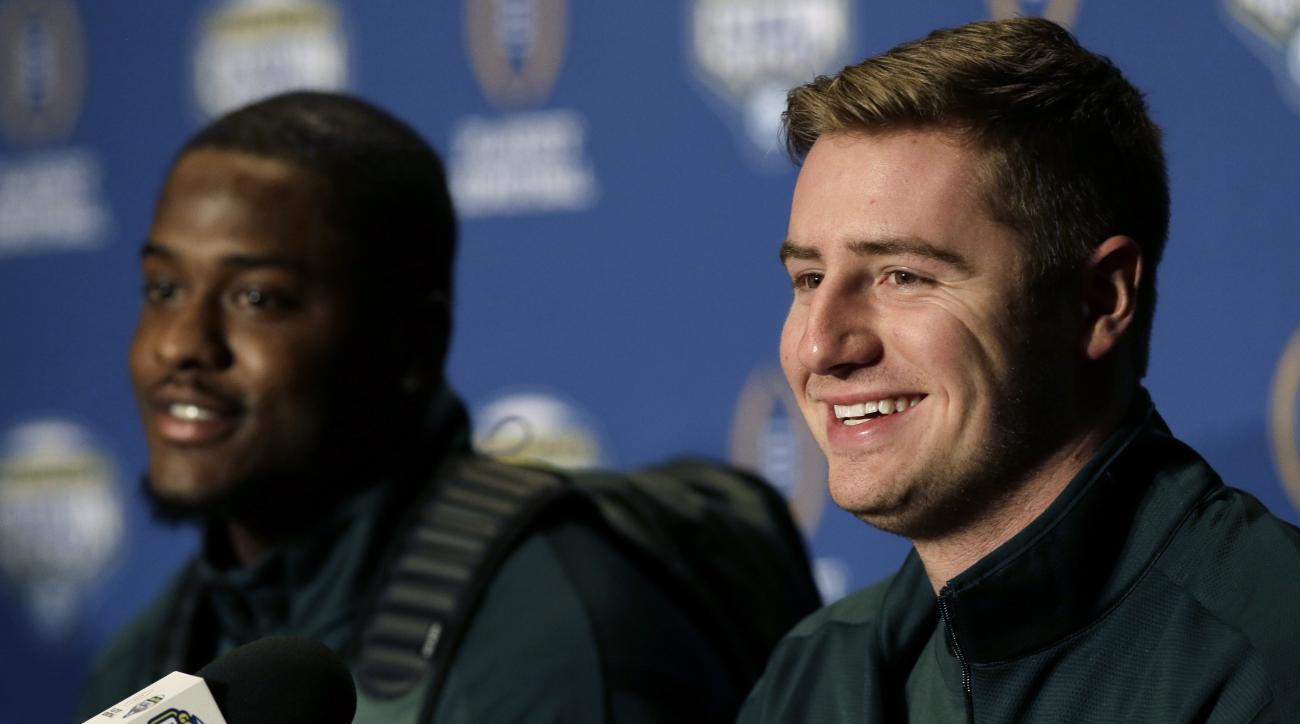 Michigan State quarterback Connor Cook, right, smiles as he sits with teammate wide receiver Aaron Burbridge  during a news conference for the NCAA Cotton Bowl college football game against Alabama Monday, Dec. 28, 2015, in Dallas. Cook says his shoulder