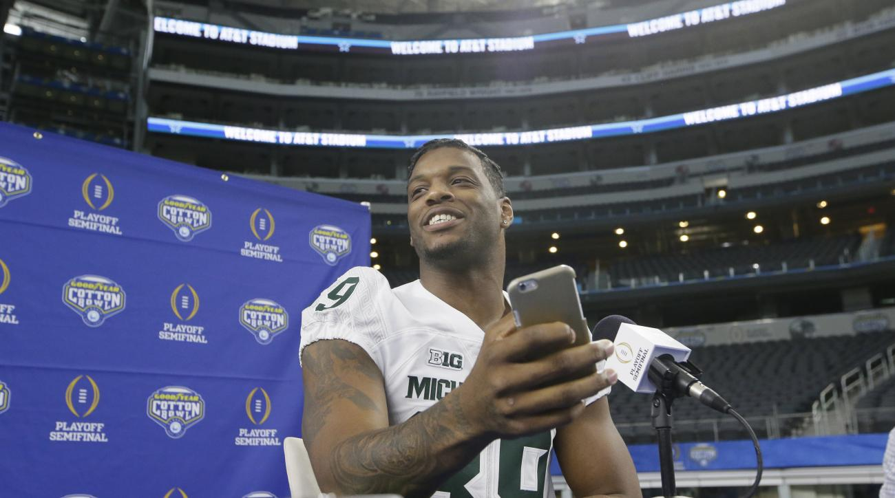 Michigan State defensive end Shilique Calhoun (89) smiles after checking his cell phone during the media day for the NCAA Cotton Bowl college football game Tuesday, Dec. 29, 2015, in Arlington, Texas. (AP Photo/LM Otero)