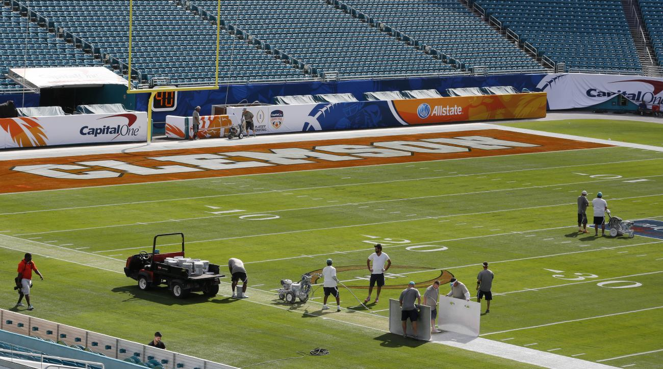 Workers paint the field for the Orange Bowl game at Sun Life Stadium Tuesday, Dec. 29, 2015, in Miami Gardens, Fla. Oklahoma is scheduled to play Clemson in the Orange Bowl NCAA college football game on New Year's Eve. (AP Photo/Joe Skipper)