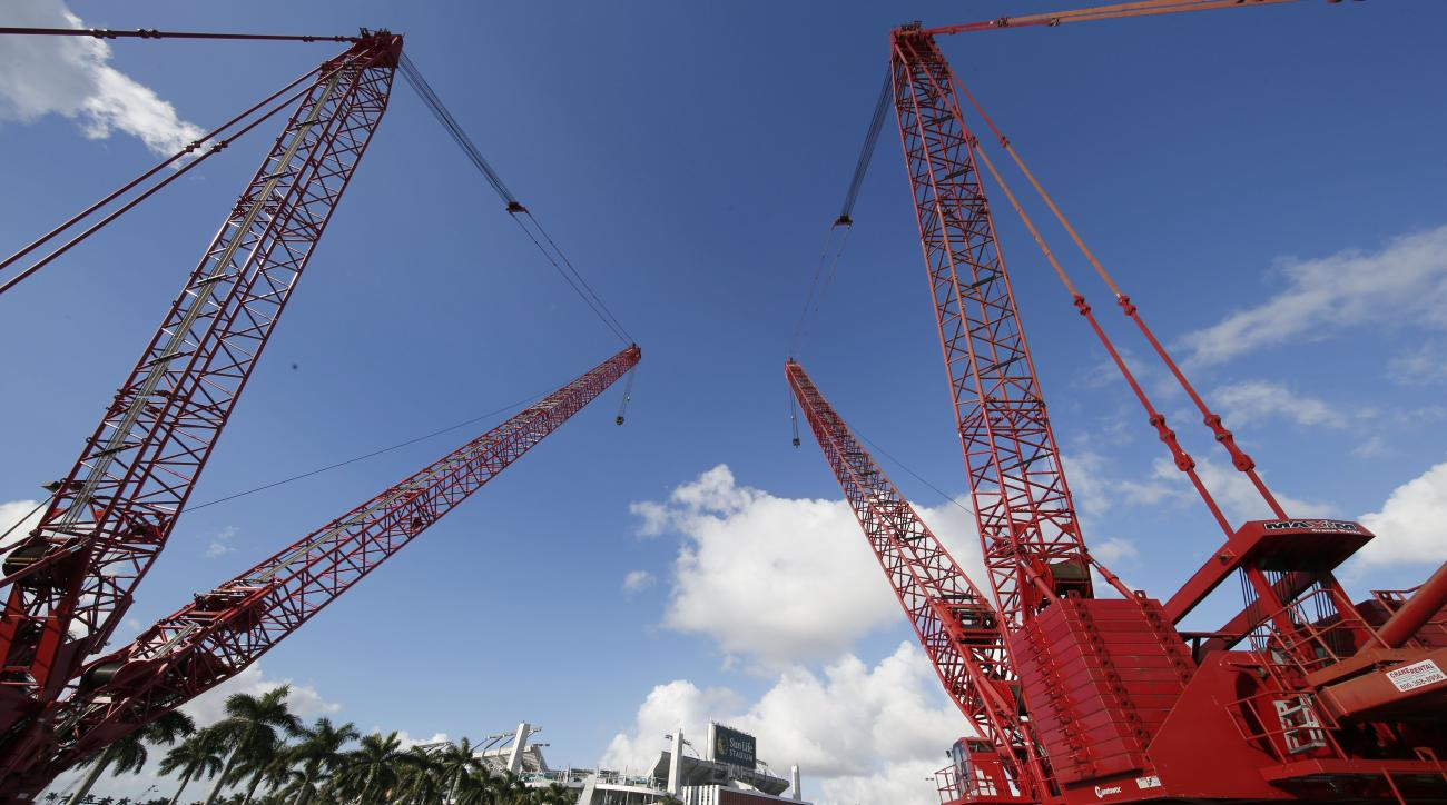 Large construction cranes sit in the parking lot of Sun Life Stadium Tuesday, Dec. 29, 2015, in Miami Gardens Fla. Oklahoma is scheduled to play Clemson in the Orange Bowl NCAA college football game on New Year's Eve. (AP Photo/Joe Skipper)