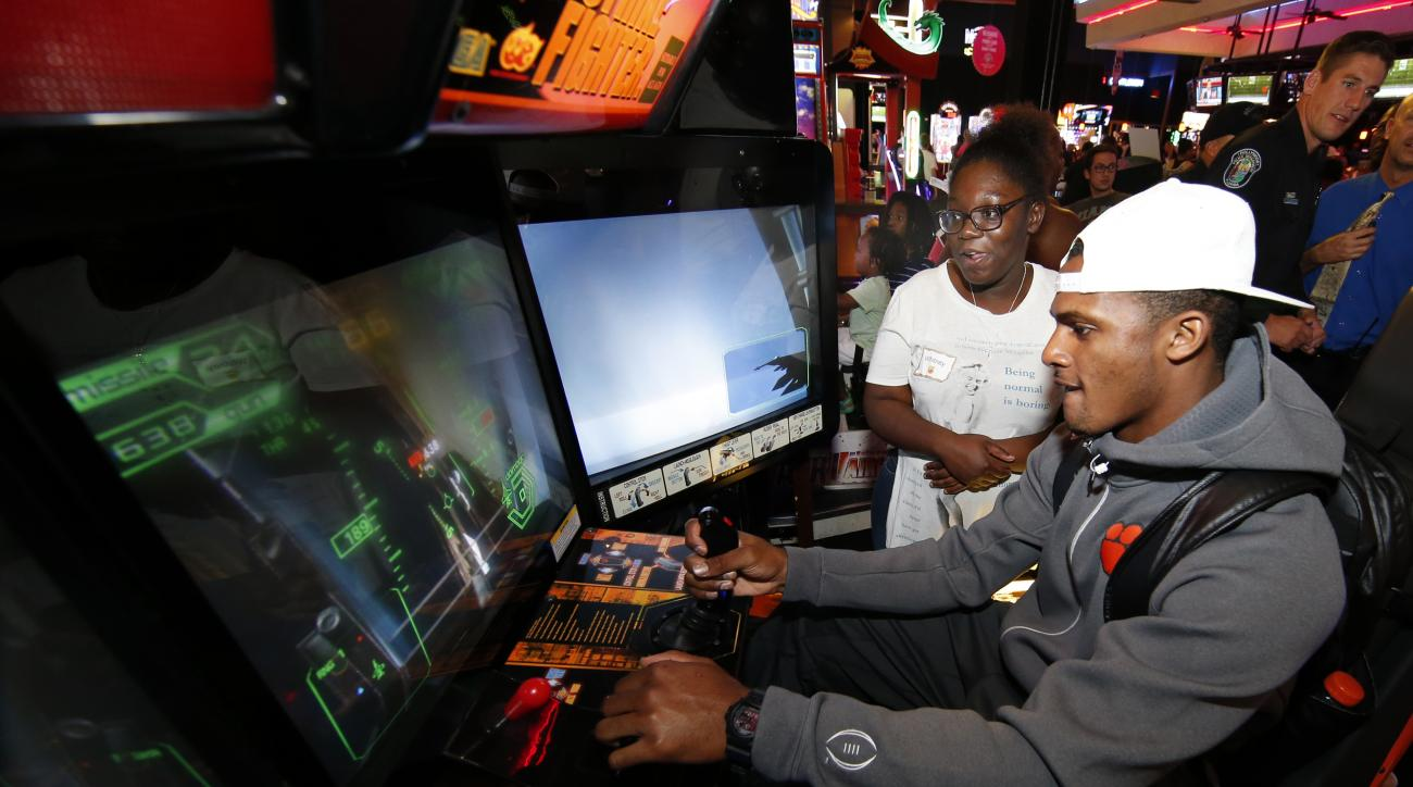 Clemson quarterback Deshaun Watson plays a video game as Whitney Similien of Boys and Girls Club looks on during an Orange Bowl outing Tuesday, Dec. 29, 2015, in Hollywood, Fla. Clemson is scheduled to play Oklahoma in the Orange Bowl NCAA college footbal
