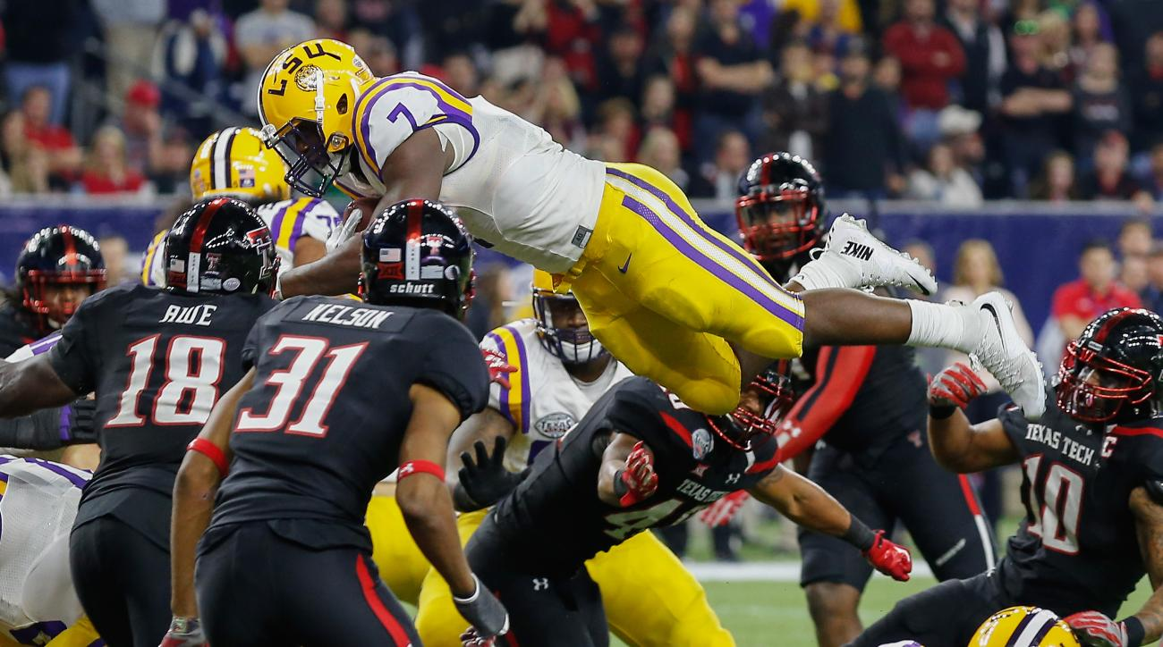 LSU running back Leonard Fournette (7) dives for a touchdown over Texas Tech linebacker Micah Awe (18) and defensive back Justis Nelson (31) during the second half of the Texas Bowl NCAA football game Tuesday, Dec. 29, 2015, in Houston. (AP Photo/Bob Leve