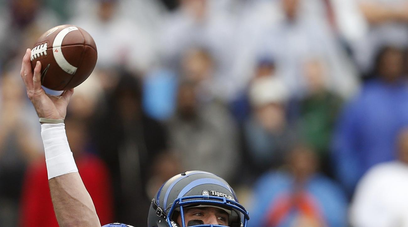 Memphis quarterback Paxton Lynch (12) throws a pass as Auburn linebacker Cassanova McKinzy (8) pressures him during the first half of the Birmingham Bowl NCAA college football game, Wednesday, Dec. 30, 2015, in Birmingham, Ala. (AP Photo/Butch Dill)