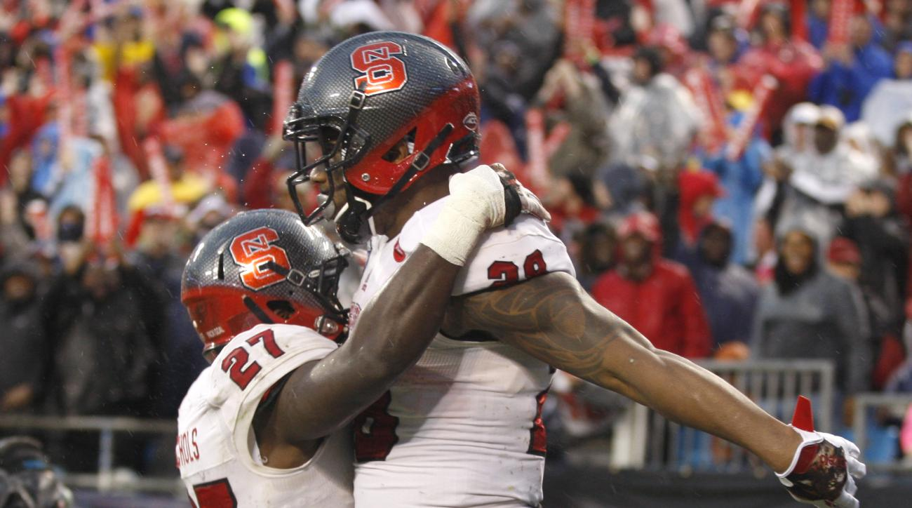 North Carolina State tight end Jaylen Samuels (28) celebrates running back Dakwa Nichols (27) after scoring a touchdown against Mississippi State in the first half of the Belk Bowl NCAA college football game in Charlotte, N.C., Wednesday, Dec. 30, 2015. (