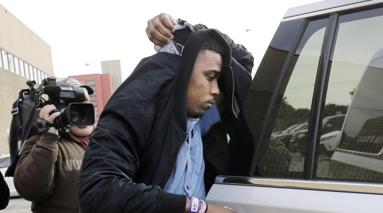 TCU quarterback Trevone Boykin holds a jacket over his head as he is escorted from a detention center after he was released on bail, Thursday, Dec. 31, 2015, in San Antonio.  Police charged Boykin with felony assault of a police officer stemming from a ba