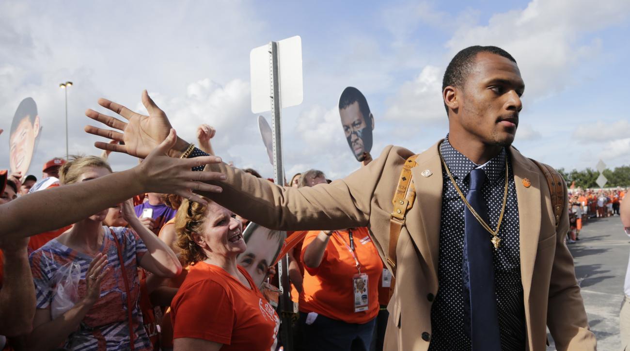 Clemson quarterback Deshaun Watson greets a fan as he arrives for the Orange Bowl NCAA college football semifinal playoff game against Oklahoma, Thursday, Dec. 31, 2015, in Miami Gardens, Fla. (AP Photo/Lynne Sladky)