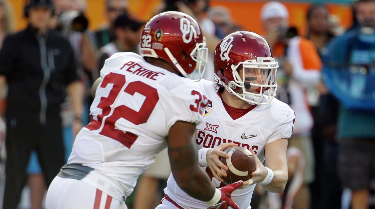Oklahoma quarterback Baker Mayfield hands the ball to Oklahoma running back Samaje Perine (32) during the first half of the Orange Bowl NCAA college football semifinal playoff game against Clemson, Thursday, Dec. 31, 2015, in Miami Gardens, Fla. (AP Photo