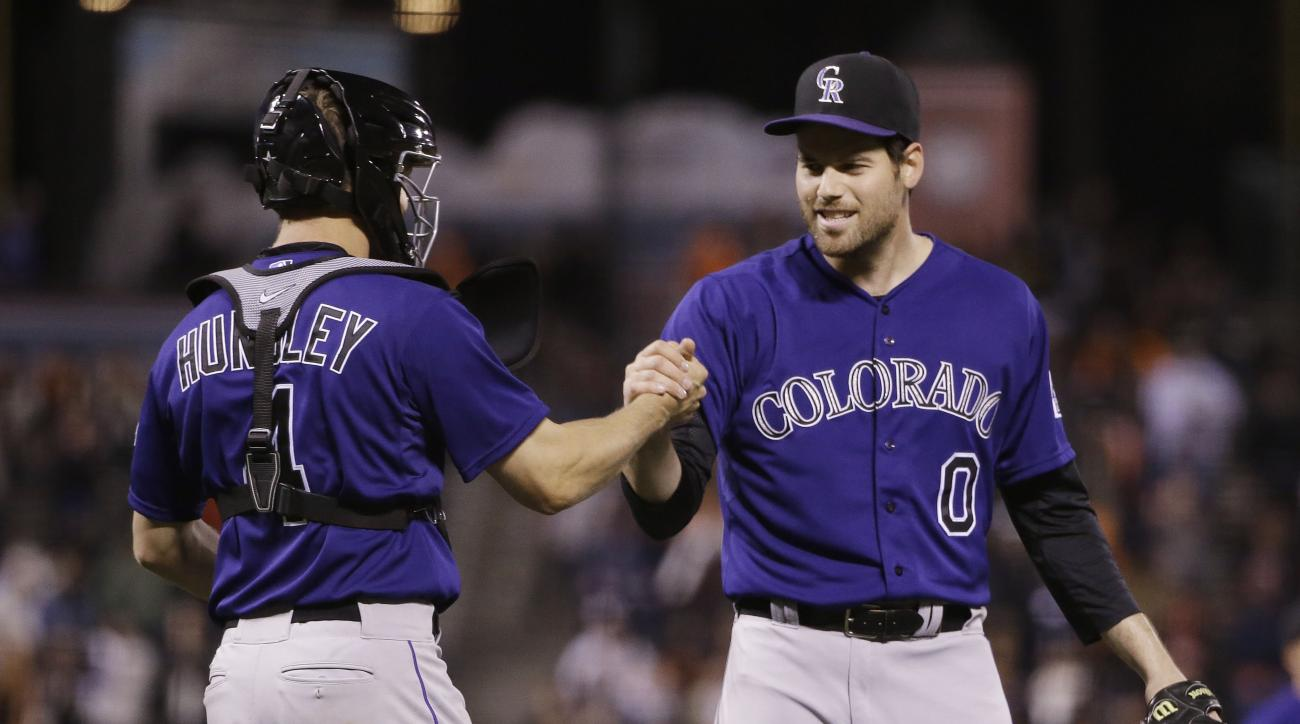 Colorado Rockies reliever Adam Ottavino, right, shakes hands with catcher Nick Hundley after recording the last out of the game against the San Francisco Giants during a baseball game on Tuesday, April 14, 2015, in San Francisco. Colorado won 4-1.  (AP Ph