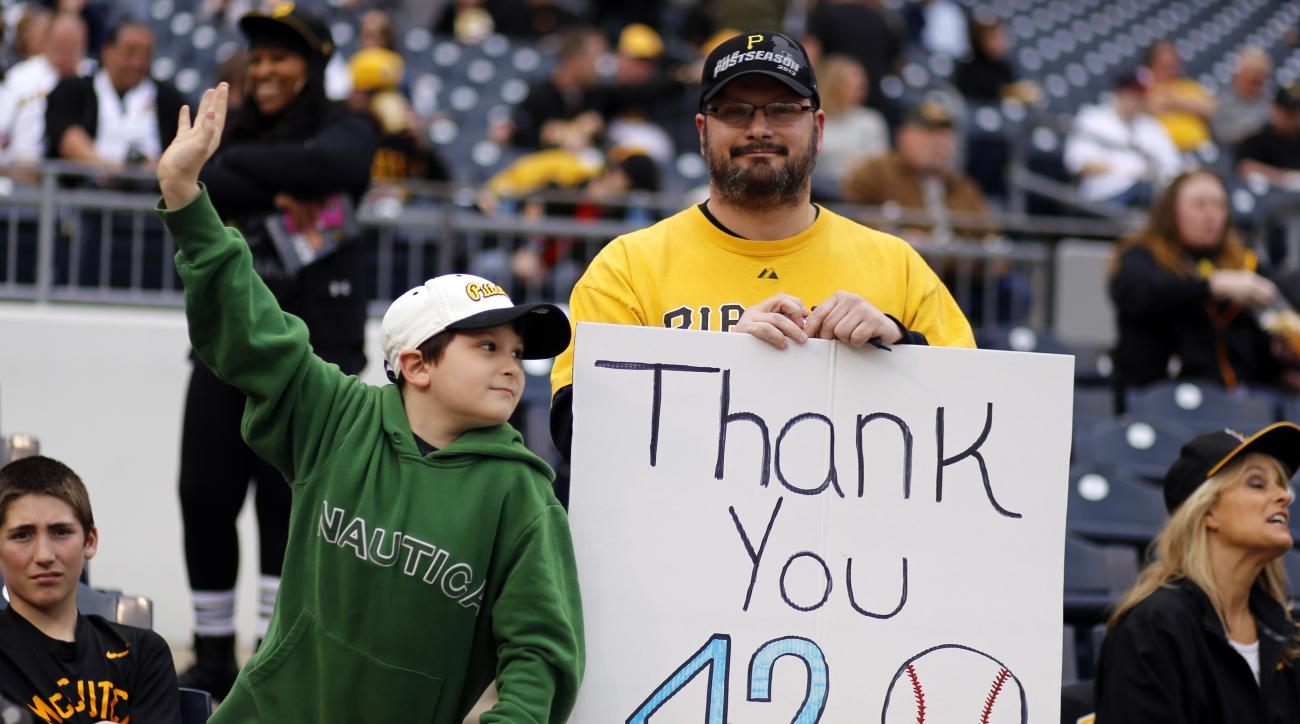 Pittsburgh Pirates fans hold a sign honoring Jackie Robinson as they watch players warm up for a baseball game between the Pittsburgh Pirates and the Detroit Tigers in Pittsburgh on Wednesday, April 15, 2015.(AP Photo/Gene J. Puskar)