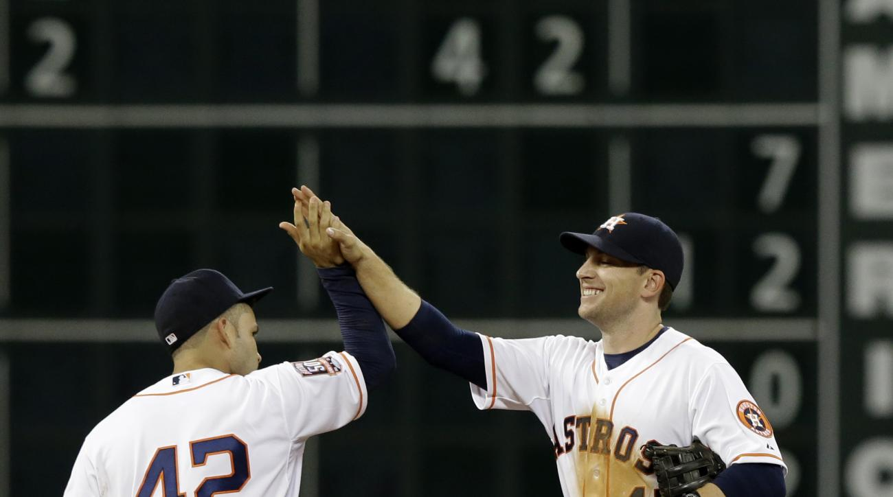 Houston Astros Jose Altuve, left, and Jed Lowrie celebrate the team's 6-1 win over the Oakland Athletics in a baseball game Wednesday, April 15, 2015, in Houston. (AP Photo/Pat Sullivan)