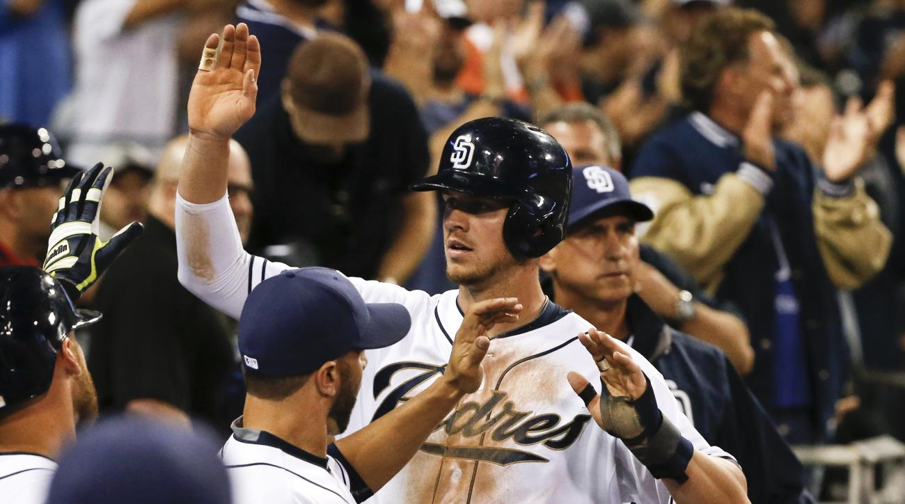 San Diego Padres' Wil Myers high fives his way through the dugout after scoring against the Arizona Diamondbacks in the sixth inning of a baseball game Wednesday, April 15, 2015 in San Diego.  (AP Photo/Lenny Ignelzi)