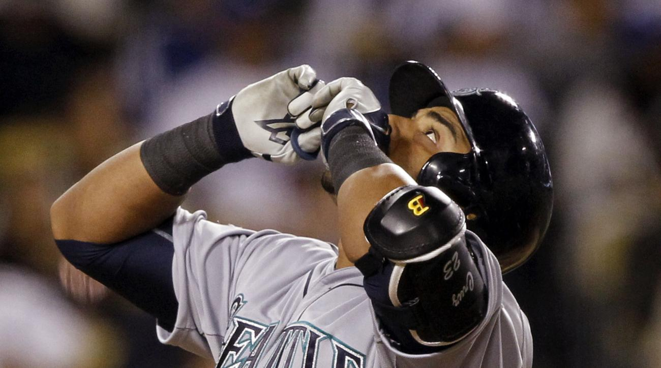 Seattle Mariners' Nelson Cruz reacts as he returns to the home plate after hitting a solo home run during the fourth inning of a baseball game against the Los Angeles Dodgers in Los Angeles, Wednesday, April 15, 2015. (AP Photo/Alex Gallardo)