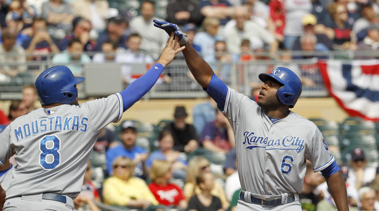 Kansas City Royals'  Lorenzo Cain (6) and Mike Moustakas (8) celebrate Cain's two-run home run off Minnesota Twins starting pitcher Tommy Milone during the first inning of a baseball game in Minneapolis, Thursday, April 16, 2015. (AP Photo/Ann Heisenfelt)