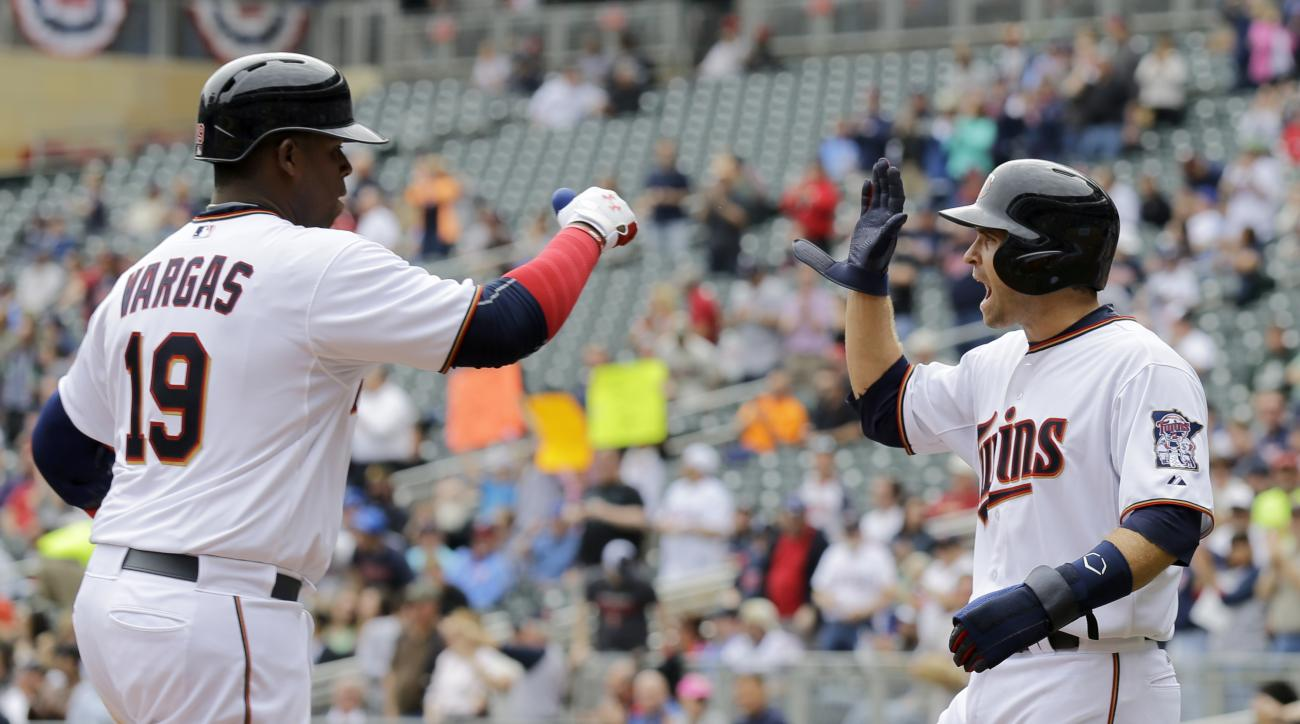 Minnesota Twins'  Brian Dozier, right, welcomes Kennys Vargas home after Vargas'  two-run home run off Kansas City Royals starting pitcher Jason Vargas during the second inning of a baseball game in Minneapolis, Thursday, April 16, 2015. (AP Photo/Ann Hei