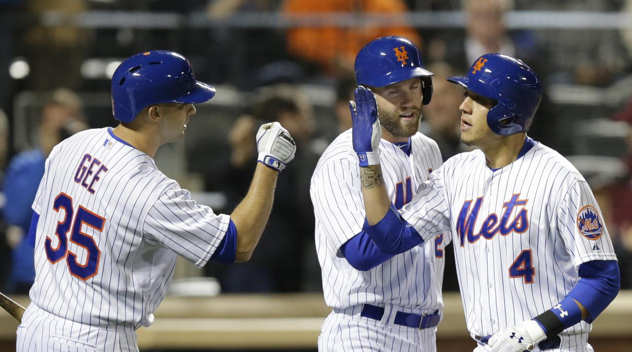 New York Mets' Dillon Gee, left, and Eric Campbell congratulate Wilmer Flores (4) after Flores hit a three-run home run in the fifth inning of the Mets' baseball game against the Miami Marlins in New York, Thursday, April 16, 2015. (AP Photo/Kathy Willens