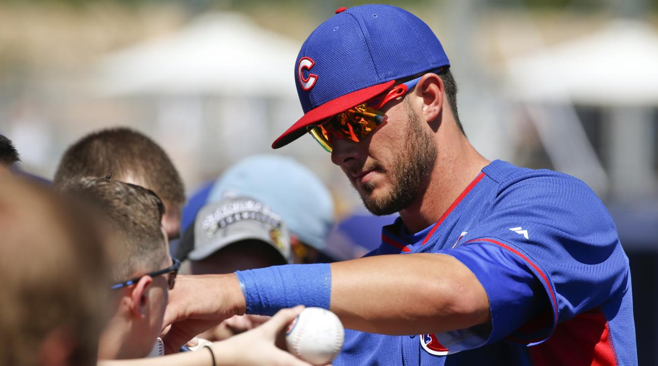 FILE - In this March 16, 2015, file photo, Chicago Cubs' Kris Bryant signs autographs before the Cubs' spring training baseball game against the San Diego Padres in Peoria, Ariz. Bryant looks to be on his way to the Cubs. Multiple outlets reported Thursda