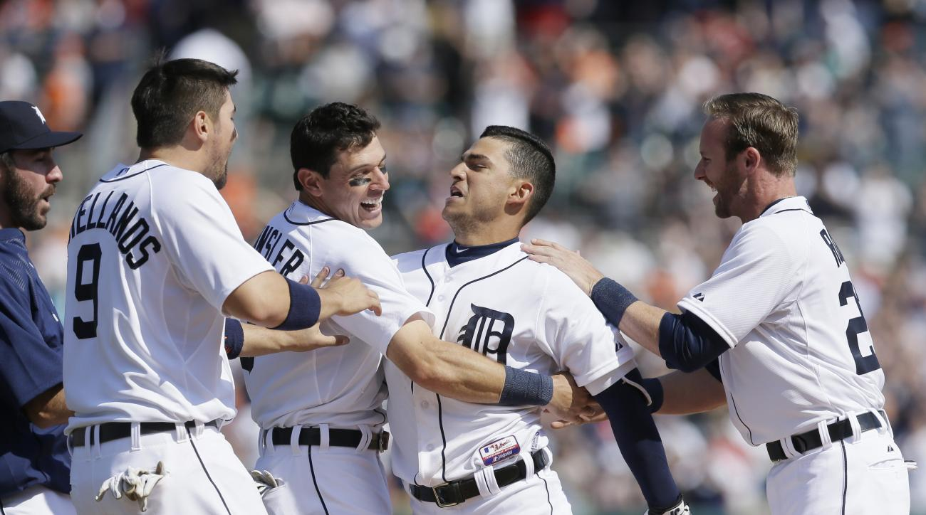 Detroit Tigers' Nick Castellanos (9), Ian Kinsler (3) and pinch runner Andrew Romine, right, hug Jose  Iglesias, second from right, after Iglesias drove in the game-winning run with a single in the ninth inning of a baseball game against the Chicago White