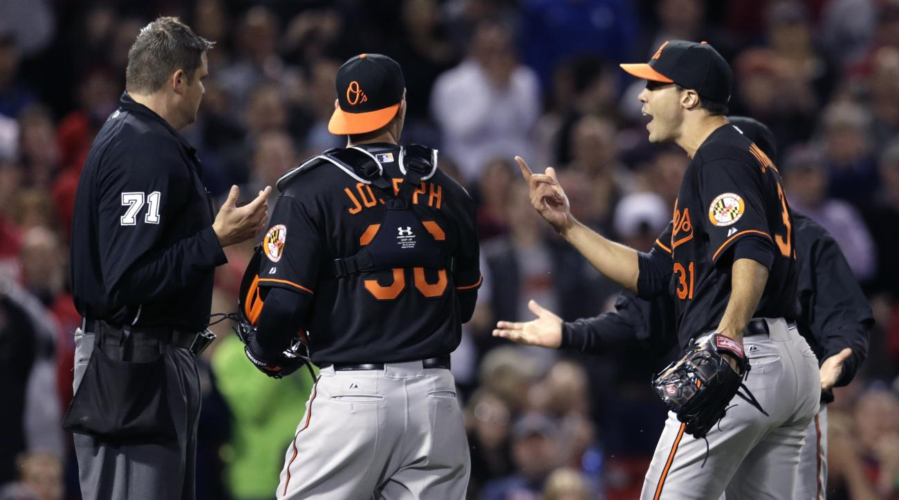 Baltimore Orioles starting pitcher Ubaldo Jimenez, right, argues with home plate umpire Jordan Baker, left, after being ejected for hitting Boston Red Sox's Pablo Sandoval with a pitch during the fourth inning of a baseball game at Fenway Park in Boston,