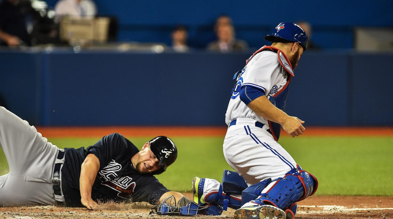 Atlanta Braves' Chris Johnson, left, scores past Toronto Blue Jays catcher Russell Martin on a hit by Andrelton Simmons Jr. during fifth-inning baseball game action in Toronto, Friday, April 17, 2015. (Aaron Vincent Elkaim\The Canadian Press via AP) MANDA