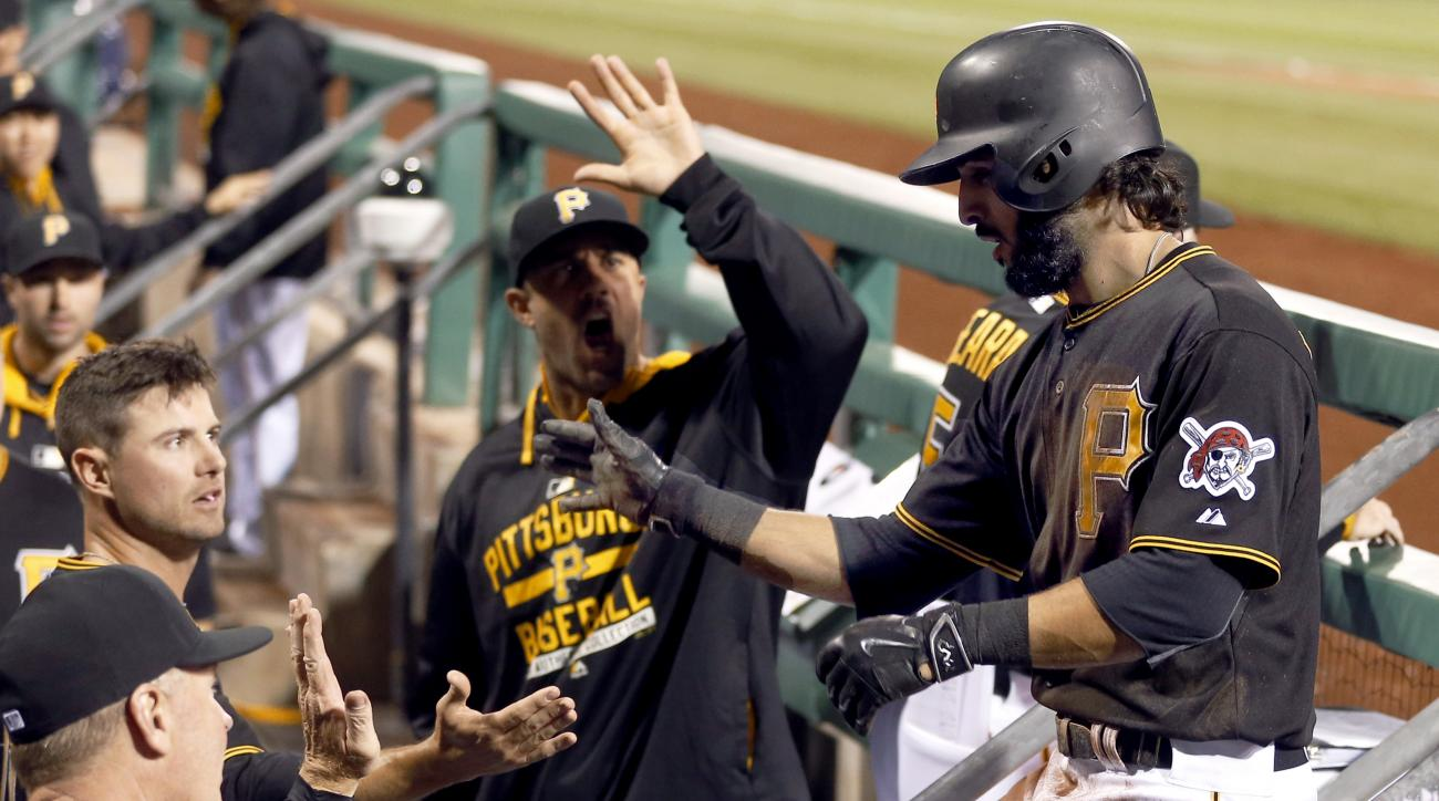 Pittsburgh Pirates' Sean Rodriguez, right, is greeted by teammates in the dugout after scoring against the Milwaukee Brewers during the fifth inning of a baseball game, Friday, April 17, 2015, in Pittsburgh. (AP Photo/Keith Srakocic)