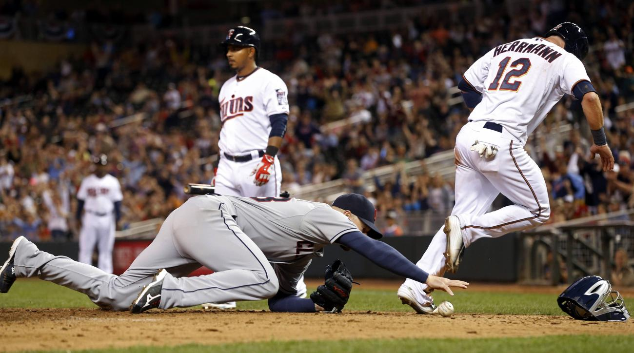 Cleveland Indians pitcher Corey Kluber, left, reaches for the ball as he covers home, allowing Minnesota Twins' Chris Herrmann, right, to score on his throw in the sixth inning of a baseball game, Friday, April 17, 2015, in Minneapolis. (AP Photo/Jim Mone