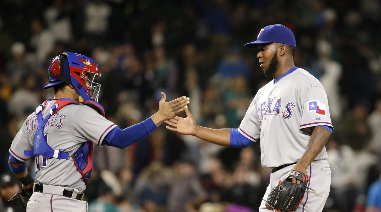 Texas Rangers closing pitcher Neftali Feliz, right, reaches toward catcher Robinson Chirinos after the Rangers defeated the Seattle Mariners 3-1 in a baseball game Friday, April 17, 2015, in Seattle. (AP Photo/Elaine Thompson)