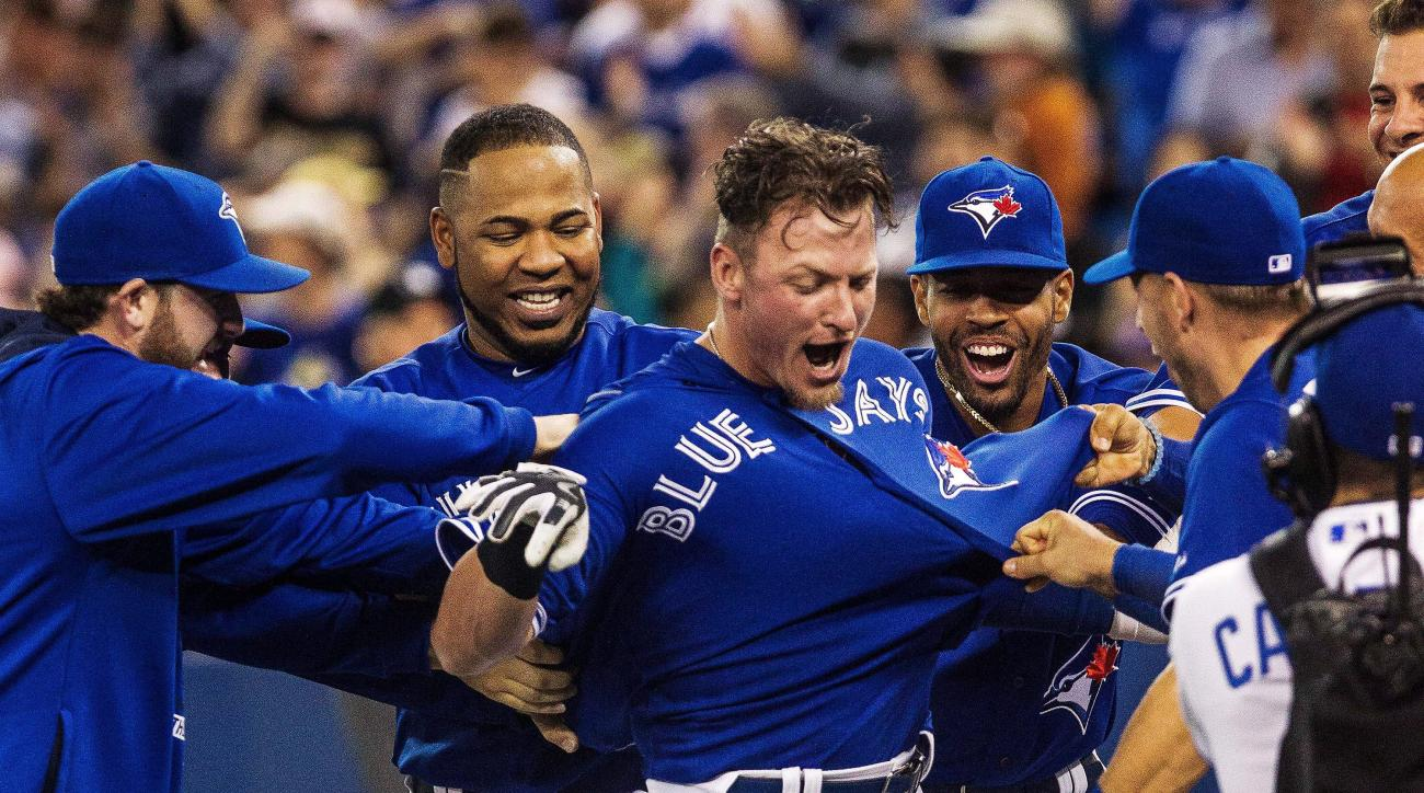 Toronto Blue Jays Josh Donaldson, center, is mobbed by his teammates as he celebrates after hitting the game-winning home run in the 10th inning against the Atlanta Braves during baseball game in Toronto Saturday, April 18, 2015. The Jays won 6-5 in 10 in
