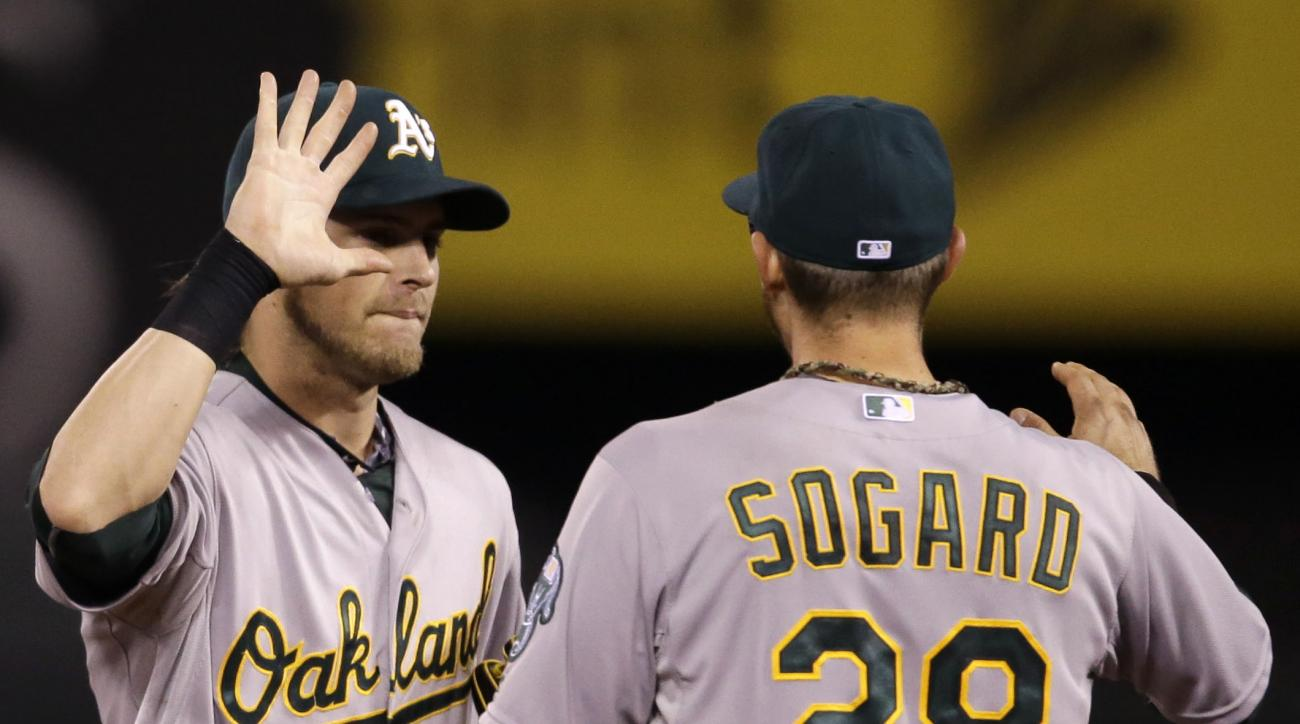 Oakland Athletics right fielder Josh Reddick, left, celebrates with second baseman Eric Sogard (28) following a baseball game against the Kansas City Royals at Kauffman Stadium in Kansas City, Mo., Saturday, April 18, 2015. The Athletics defeated the Roya