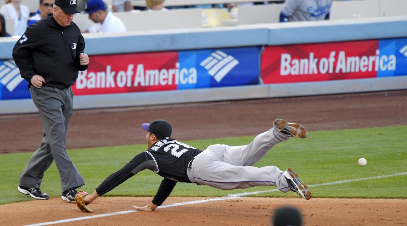 Colorado Rockies third baseman Nolan Arenado, top right, cannot reach a ball hit for a double by Los Angeles Dodgers' Howie Kendrick during the second inning of a baseball game, Saturday, April 18, 2015, in Los Angeles. (AP Photo/Mark J. Terrill)