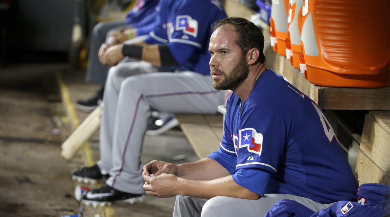 Texas Rangers starting pitcher Colby Lewis sits in the dugout after he was pulled in the sixth inning of a baseball game against the Seattle Mariners, Saturday, April 18, 2015, in Seattle. (AP Photo/Ted S. Warren)